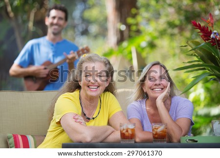 Pair of laughing female friends near ukulele player outdoors - stock photo