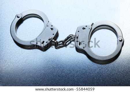 Pair of locked handcuffs shot on steely cool metallic background - stock photo