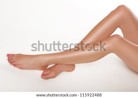 Pair of long sexy sliky smooth female legs extending into the frame from the right over white