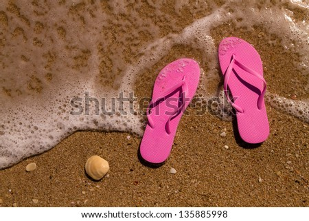Pair of magenta pink flip flops laying on the sand with ocean wave washing up on the beach - stock photo