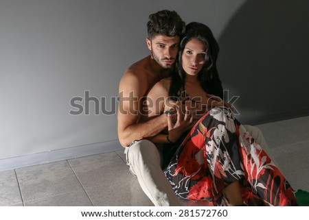 Pair of models sitting on the floor, posing for the camera, in a dark and empty house. - stock photo