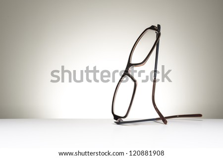 Pair of modern fashionable spectacles balanced in an upright position on a white studio background with copyspace conceptual of vision, correction, optometry and healthcare - stock photo