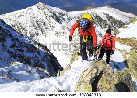 Pair of mountain climbers on snowy ridge in winter - stock photo