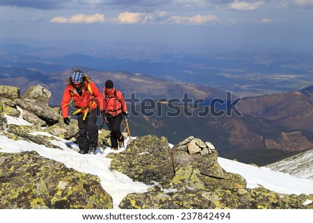 Pair of mountaineers climb on snow covered mountain  - stock photo