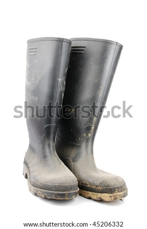 pair of muddy farmer boots isolated on a white background