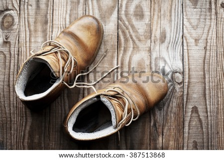 Pair of old boots view from above on rustic wooden background