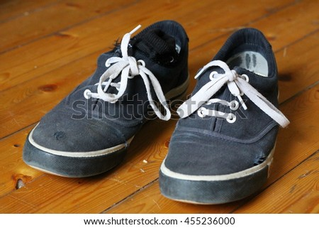 Pair of old dark blue canvas shoes on the wooden floor - stock photo