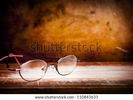 Pair of old eyglasses on a wooden desk with a grunge background