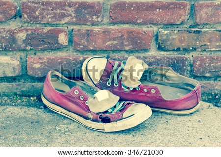 Pair of old smelly worn classic sneakers leaning against a brick wall - stock photo