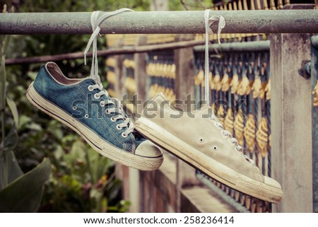 pair of old sneakers hang, process color - stock photo