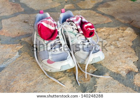 pair of old used running shoes with socks - stock photo