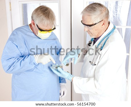 pair of older doctors consulting over a culture growth in a petri dish - stock photo