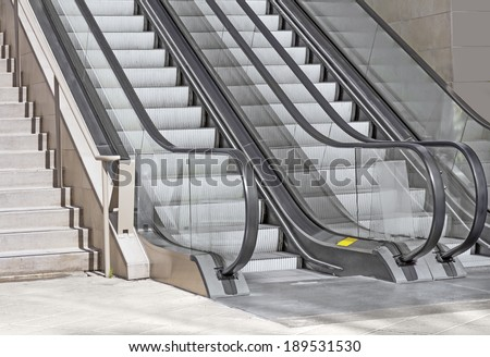 Pair of outdoor modern escalators next to a stone stairway, stone tile floor.Gray metal textured steps, black handrail. Clear acrylic or plastic sides.  - stock photo
