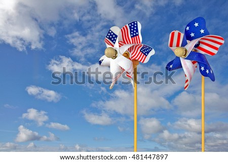 pair of patriotic flag pinwheels on summer sky background