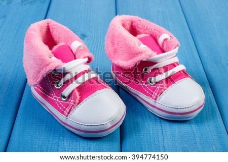 Pair of pink baby shoes on blue boards, concept of extending family and expecting for baby