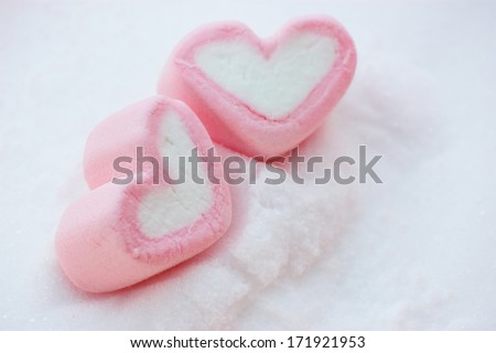 pair of pink heart shape marshmallow on snow