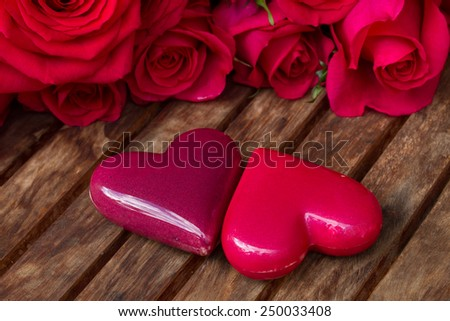 pair of pink hearts with roses   on wooden  table - stock photo