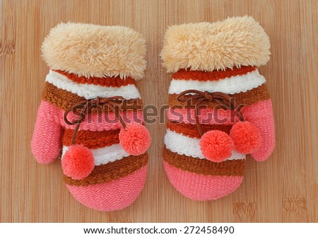 pair of pink knitted wool mittens on wooden desk  - stock photo