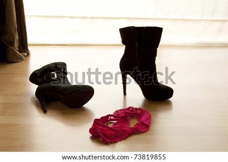 pair of pink panties on a wooden floor next to a high heel boot - stock photo