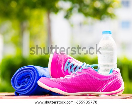 Pair of pink sport shoes towel water bottle on wooden board. In the background forest or park trail. Accessories for running sport.