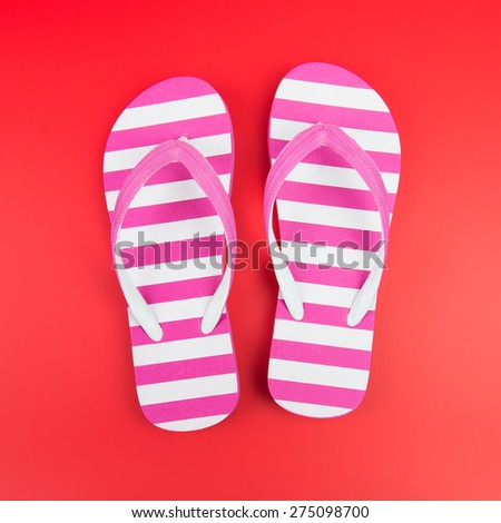 Pair of pink striped flip flop on red background - stock photo