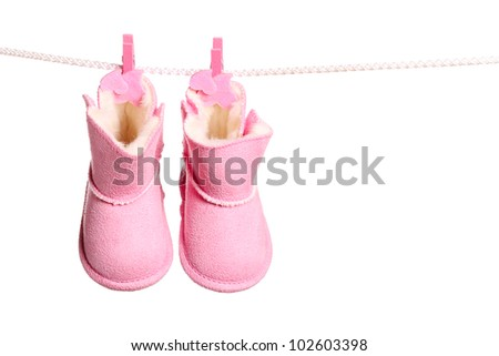 Pair of pink winter boots hanging on the clothesline. Image isolated on white background - stock photo