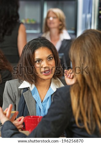 Pair of professional women talking at coffee house - stock photo