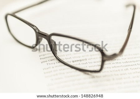 Pair of Reading Glasses with Text Just Visible