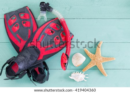 Pair of red and black adult flippers and mouthpiece for skindiving with seashells and a starfish on a muted green stained wooden deck conceptual of a summer vacation and activity - stock photo