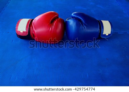 Pair of Red and Blue boxing gloves hanging on a Blue wall - stock photo