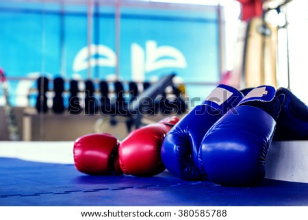 Pair of Red and Blue boxing gloves hanging on a Blue wall fitness center - stock photo