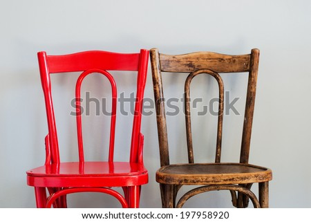 Pair of Red and Brown Chairs on a Grey Wall - stock photo