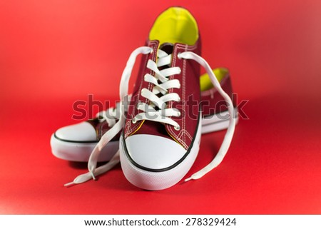 Pair of red canvas trainers on a maroon background - stock photo
