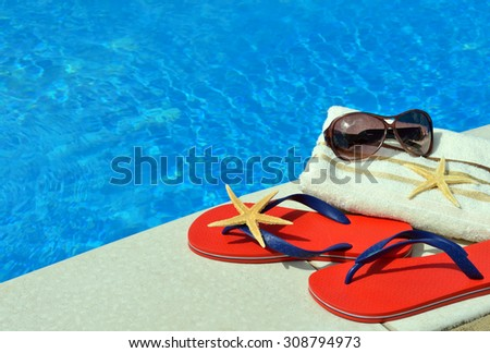 Pair of red flip-flops, sunglasses, towel, starfish on the swimming pool