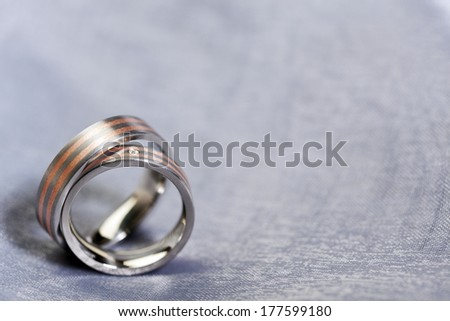 pair of red gold and platinum wedding rings on silver cloth with copy space, shallow depth of field