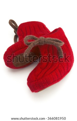 Pair of red knitted baby shoes on white background - stock photo