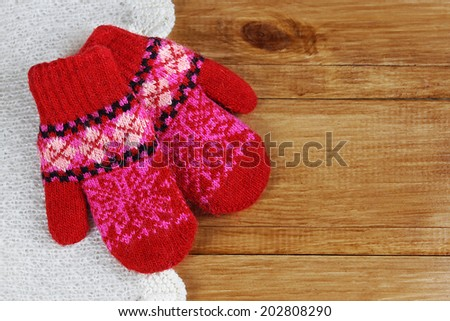 pair of red knitted wool mittens on wooden desk  - stock photo