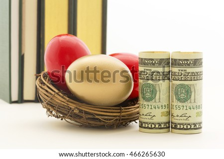 Pair of red nest eggs and two, symbolic American dollars reflect risks and dangers in business and investments.  Gold nest egg shows benefit of diversified portfolio.