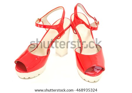 Pair of red womens high heeled shoes on white background.