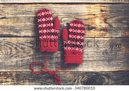 Pair of red woolen mittens on rustic wooden background - stock photo