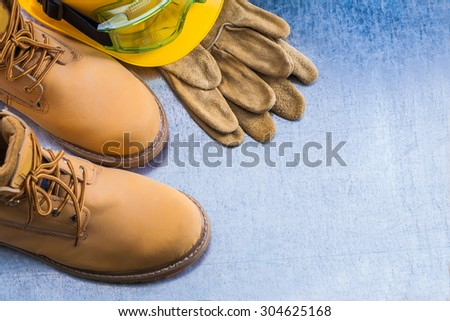 Pair of safety lace boots leather gloves hard hat and working goggles on scratched metallic background construction concept. - stock photo