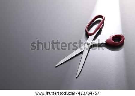 pair of scissors on the gray background
