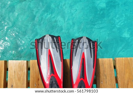 Pair of scuba fins on the pier above the tropical sea. Red fins over the blue water. Tropical paradise close to the sea. Scuba vacation on the tropical island.