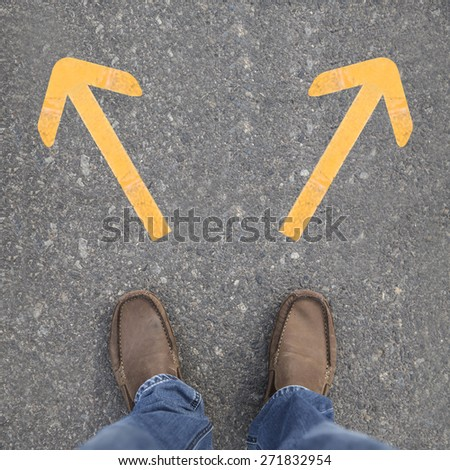 Pair of shoes on a road with yellow arrows - stock photo