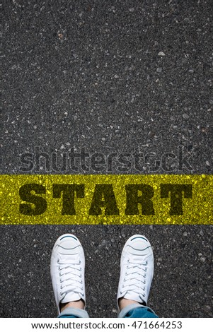 Pair of shoes standing on a road with the word START on the yellow background