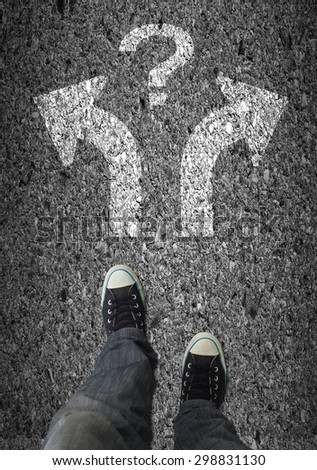 Pair of shoes standing on a road with two arrow and the question mark on asphalt background - stock photo