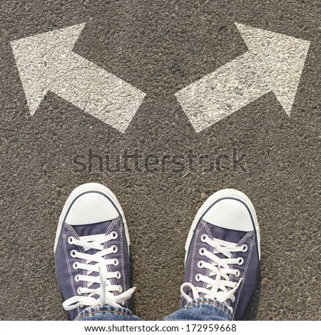 Pair of shoes standing on a road with two white arrow - stock photo