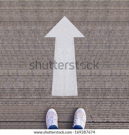 Pair of shoes standing on walkway with arrow - stock photo