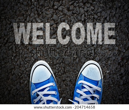 Pair of shoes standing on walkway with WELCOME - stock photo