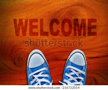 Pair of shoes standing on wood with WELCOME
